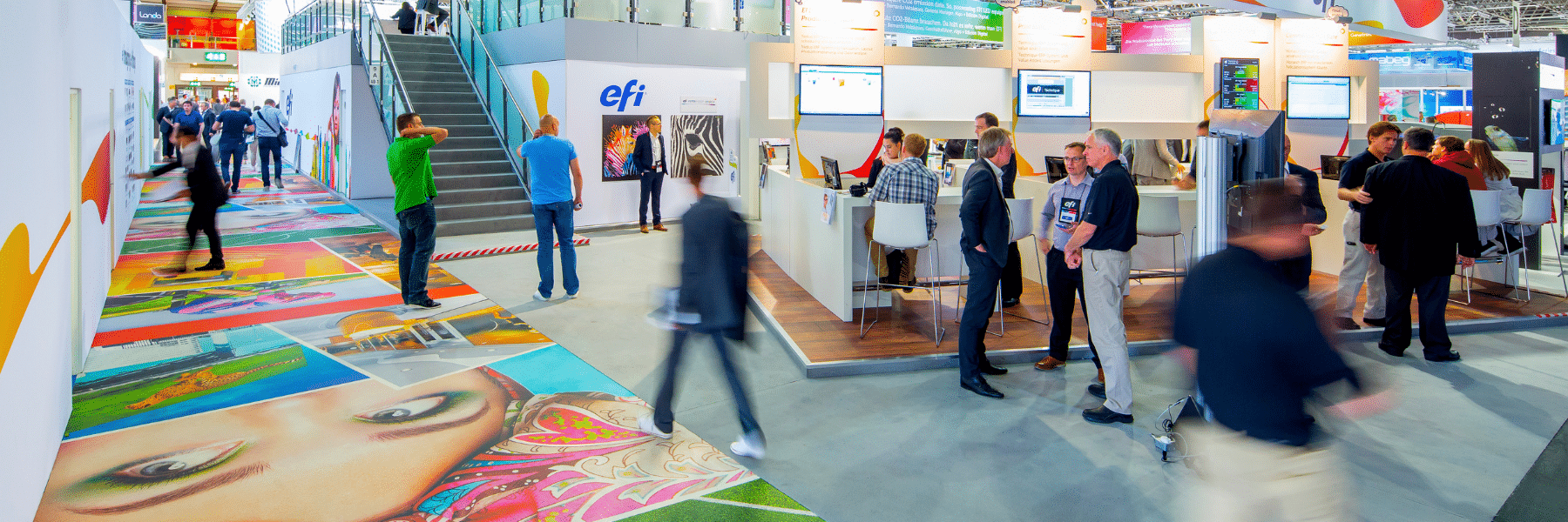 People walking through booths on the EFI Drupa show floor